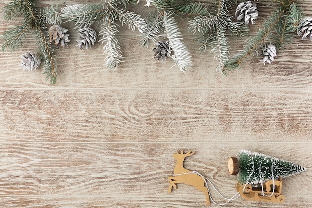 木製のホワイトボードに松ぼっくりと雪とクリスマスのモミの木。そりでモミの木を運ぶクリスマスのトナカイ。冬の背景