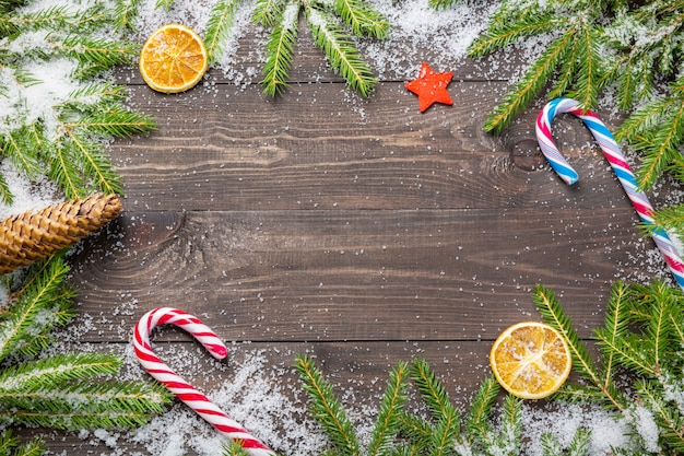 Christmas fir trees in snow with cone, candy canes, decorative star and dried oranges on a dark wooden board