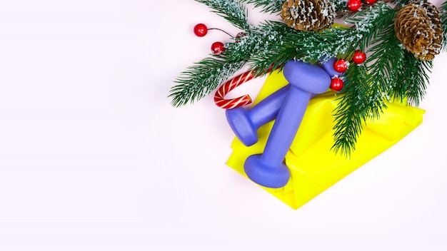 Christmas fitness. healthy and active lifestyles  concept. purple dumbbells, yellow rubber band, candy and fir-tree on pink