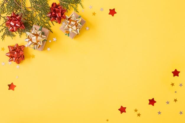 크리스마스 플랫 누워 배경입니다. 노란색에 반짝이, 장식, 별 색종이 조각이 있는 선물 상자.