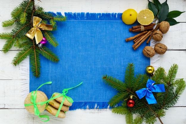 クリスマスフラットレイ。枝トウヒ、装飾品、レモンクッキー、ナッツ、シナモン、柑橘類
