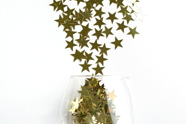 クリスマスフラットレイシャンパングラスは、コピースペースで金色の星の紙吹雪を注ぎました。新年の上面図の背景