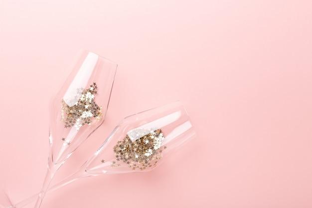 Рождественская плоская планировка. бокалы для шампанского и золотые украшения на розовом фоне - изображение