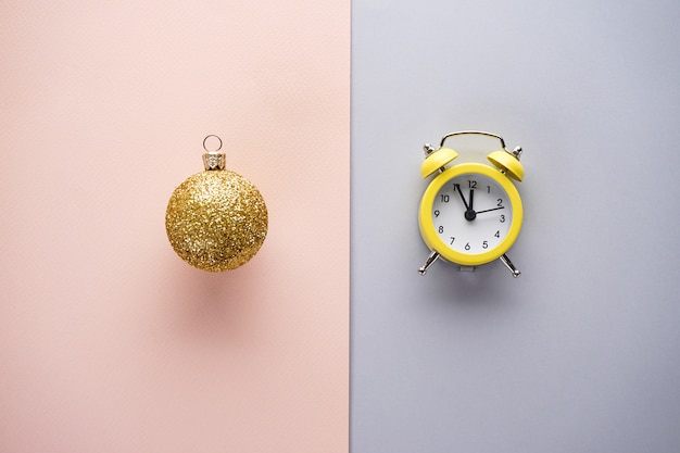 Christmas flat lay composition. christmas yellow alarm clock and golden toy
