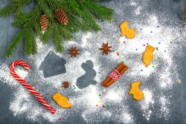 Christmas flat lay composition. flour silhouette of cookies on dark background among christmas tree branches, cones, star anise, cinnamon and candy cane. christmas, winter holidays, new year concept.