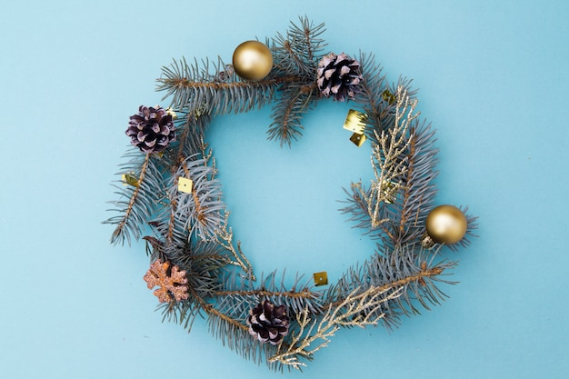 Christmas flat lay composition in the form of a wreath. branches of blue spruce, cones, toys on a blue background. christmas, winter, new year concept. top view, .