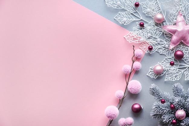クリスマスフラットは、コピースペースとピンクとシルバーの2色の背景に横たわっていた。光沢のある幾何学的な葉と柔らかい繊維のつまらないもの、散りばめられたガラスのクリスマスボールが飾られた装飾的な白い冬の小枝。