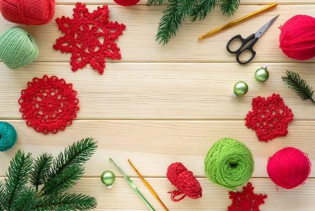 Christmas flat lay of items for needlework. knitted snowflakes, threads and hooks on wooden background.