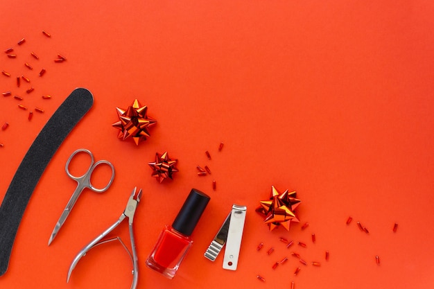 Christmas flat lay of manicure accessories and nail polish with holiday decorations on a red background. space for text.