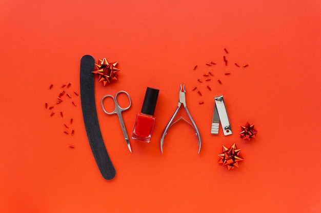 Christmas flat lay of manicure accessories and nail polish with holiday decorations on a red background.