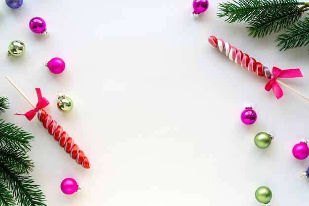 Рождественская плоская планировка леденцов, шариков и еловых веток на белом фоне. место для текста.