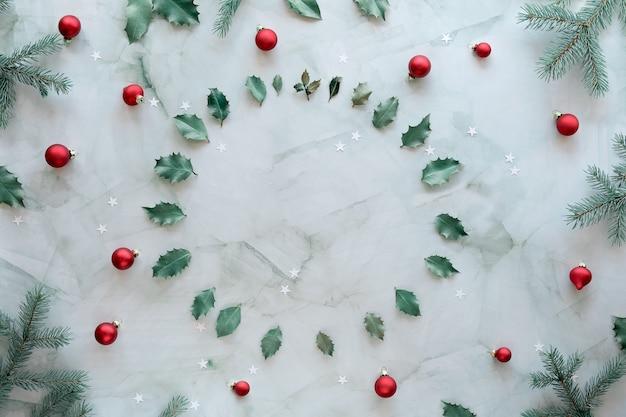 Рождественская квартира лежала на мраморном столе, копировальное пространство. рождественский фон в зеленом, белом и красном. натуральные еловые веточки, листья падуба и стеклянные безделушки.