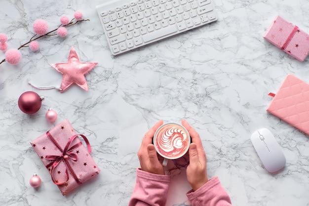크리스마스 플랫 대리석 테이블에 누워. 카페 라떼 또는 핫 초콜릿의 따뜻한 컵에서 심장 모양으로 워밍업하는 손. 겨울 장식 : 전나무 나뭇 가지, 별 및 분홍색 장신구, 복사 공간