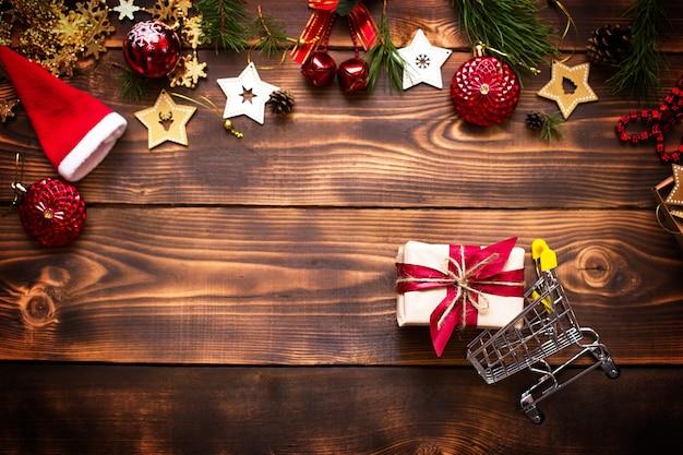 Новогодняя квартира оформлена на тему шоппинга, покупки подарков на новый год. черная пятница, распродажа, декор из звездочек, еловых веток, шарика, бус, гирлянд, шишек на деревянном фоне. место для текста
