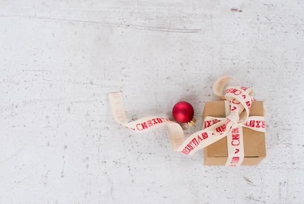 Рождественская плоская сцена в стиле - настоящая коробка с красным шаром на деревянном белом столе