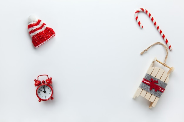 Christmas flat lay, winter beanie hat, candy cane, small red analog clock, sled on white background