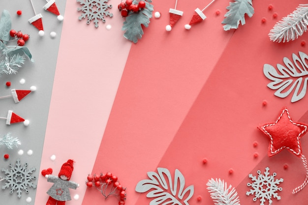 Christmas flat lay with frame from decorations - winter leaves, dolls, garland and snowflakes. above view of multicolored geometric layered paper background in red, orange, pink, magenta and silver.