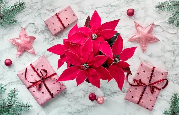 鮮やかなフクシア色のポインセチア、包まれたギフトボックス、天然の緑のモミの小枝、ピンクの装身具で作られたフレームを備えたクリスマスフラットレイアウト