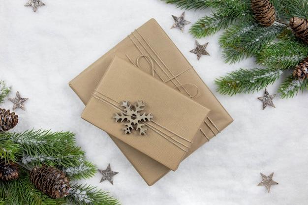 크리스마스 평면 녹색 소나무 가지와 눈 배경에 포장 된 선물 누워