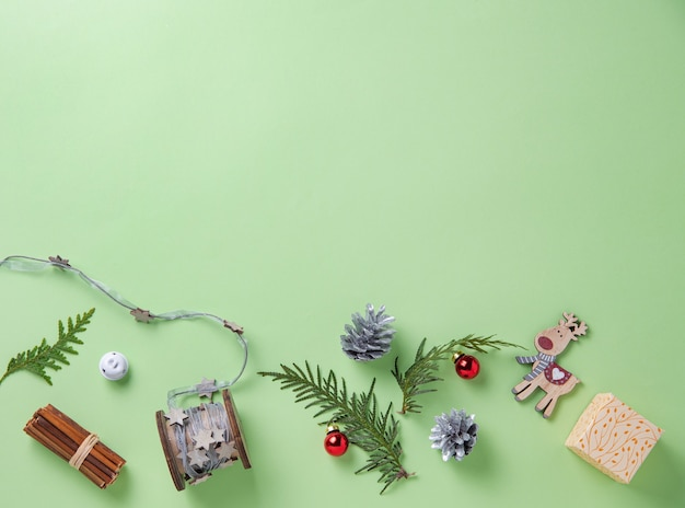 Christmas flat lay  with green tree, red balls, wooden toys,  and box present on green background. image  top view and copy space