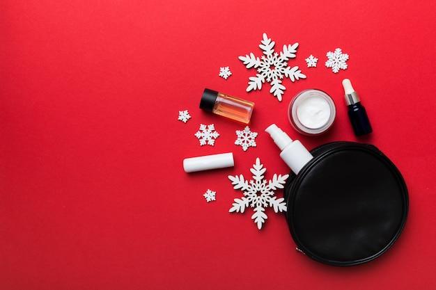 크리스마스 납작한 배경에는 화장용 가방에 화장용 화장품이 들어 있습니다. 상위 뷰 새 해 뷰티 개념입니다.