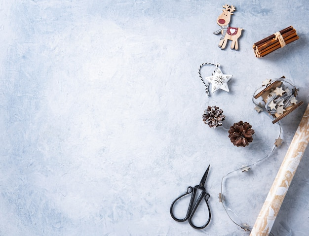 Christmas flat lay  with paper, scissors, red balls and  wooden toys on blue  background. image  top view and copy space
