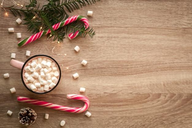クリスマスフラットはマシュマロとキャンディーとコーヒーのピンクのカップで横たわっていた