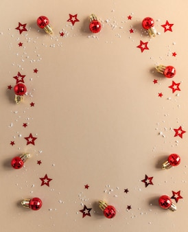 크리스마스 플랫 베이지 색 배경에 빨간색 크리스마스 공, 색종이와 인공 눈이 누워. 평면도. 복사 공간