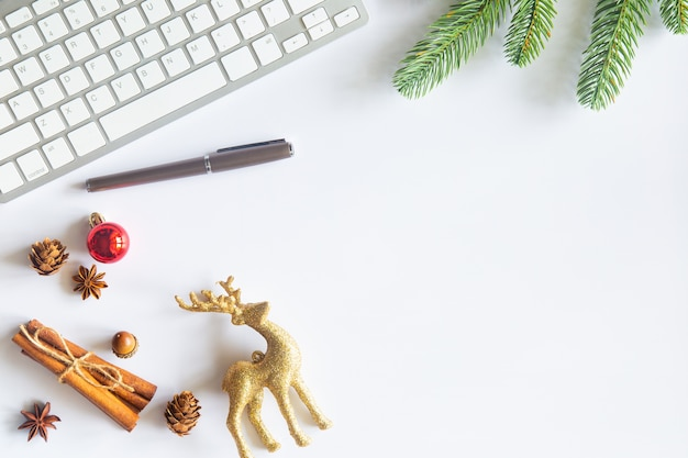 Christmas flat lay with reindeer, tree branch, pen and keyboard