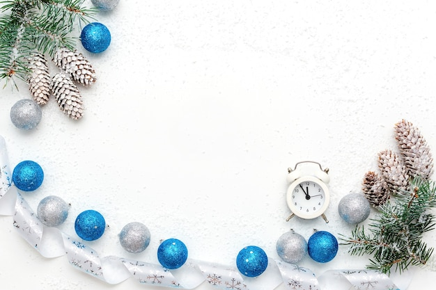 Christmas flat lay with white alarm clock, snow branches of blue spruce, fir cones, blue and silver christmas balls and white ribbon on white