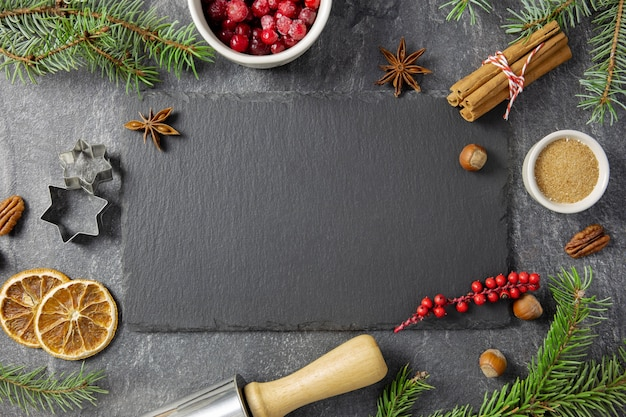 Christmas flat lay with winter spices and ingredients for baking on dark background.