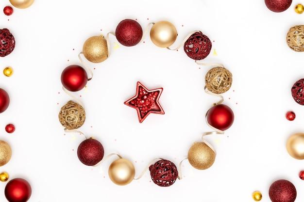 赤と金色のクリスマスの飾りで作られた花輪とクリスマスフラットレイ