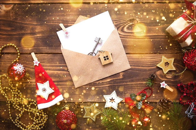 Christmas flat lay on a wooden background with keys to new house in the center with a envelope with a note sheet