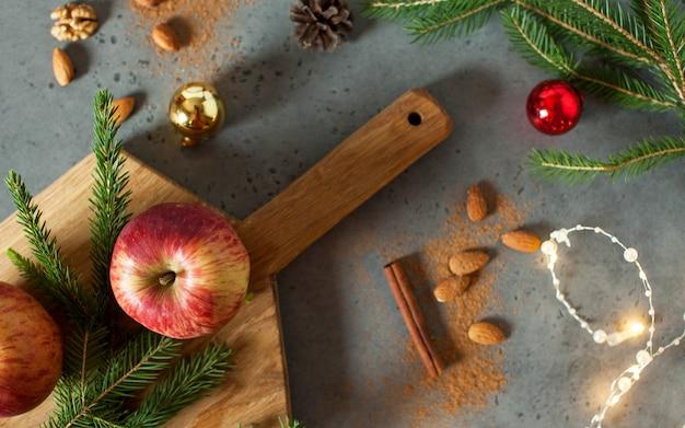 リンゴ、ナッツ、シナモン、木の枝のクリスマスフラットレイ。クリスマスと新年のコンセプトです。グリーティングカード。