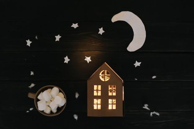 Рождественский плоский с бумажными лунными звездами и домом на деревянном фоне, вид сверху