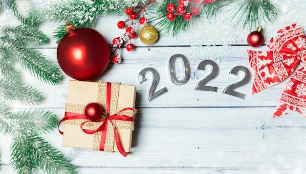 明るい木製の背景にギフト新年のおもちゃと番号2022とクリスマスフラットリー