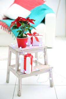 クリスマスの花のポインセチアとクリスマスの装飾が施された装飾的なはしごの装飾、明るい背景