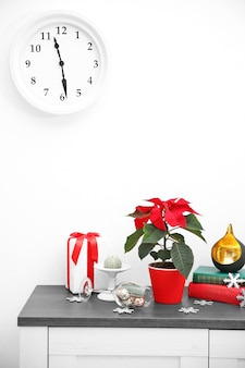 크리스마스 꽃 포인세티아와 크리스마스 장식이 있는 선반 위의 장식, 밝은 배경