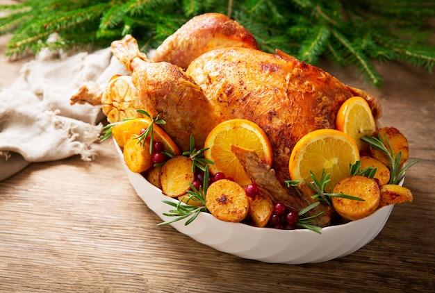 クリスマス料理。木製のテーブルの上にジャガイモ、オレンジ、クランベリーを添えて焼きたての七面鳥