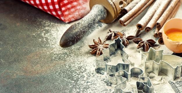 크리스마스 음식. 베이킹 재료, 향신료 및 통행료. 밀가루, 계란, 롤링 핀 및 쿠키 커터. 빈티지 스타일 톤 그림