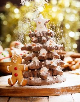 Рождественская еда. рождественская елка из пряников и снега из сахарной пудры на размытом фоне