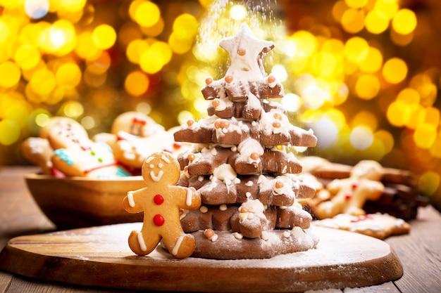 ジンジャーブレッドクッキーと粉砂糖で作った雪で作ったクリスマスフードクリスマスツリー