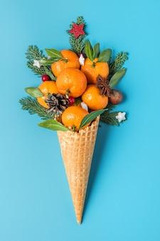 Концепция рождественской еды. мандариновые плоды, еловые ветви и рождественские украшения в вафельном рожке мороженого на синем фоне. вертикальная ориентация. вид сверху. плоская планировка