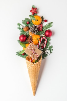 クリスマス料理のコンセプト。みかんの果実、モミの木の枝、白い背景の上のワッフルアイスクリームコーンのクリスマスの装飾。垂直方向。上面図。フラットレイ