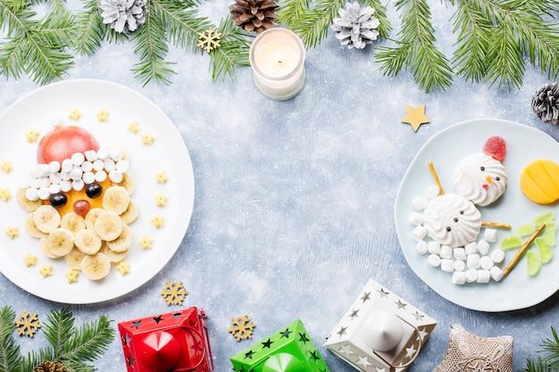 子供のためのクリスマス料理-キウイのクリスマスツリー、マシュマロの雪だるま、バナナのサンタクロース。上面図