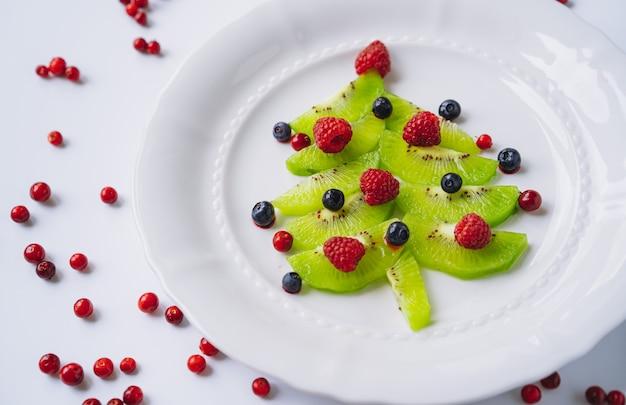 Рождественские блюда для детей. белое блюдо с елкой из киви, малины, брусники и черники. фото высокого качества