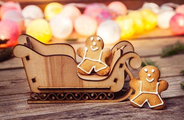 Рождественская еда. пряничный человечек. гирлянда. сани санты на деревянном столе