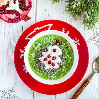 크리스마스 음식 건강한 아이디어. 코코넛과 석류로 만든 크리스마스 트리로 장식된 그린 스무디. 건강 또는 어린이 음식 개념