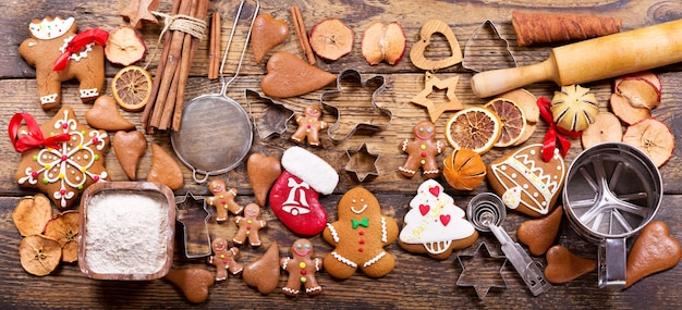 Рождественская еда. домашнее печенье пряничный человечек с ингредиентами для рождественской кулинарии и кухонной утварью на деревянном столе, вид сверху