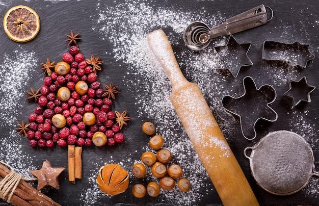 Рождественская еда. ингредиенты для приготовления рождественской выпечки: ель из сушеной клюквы с орехами, кухонная утварь и сухофрукты на темном столе, вид сверху